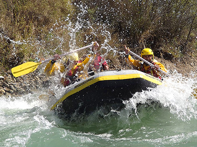 Some people riding a raft on white water rapids