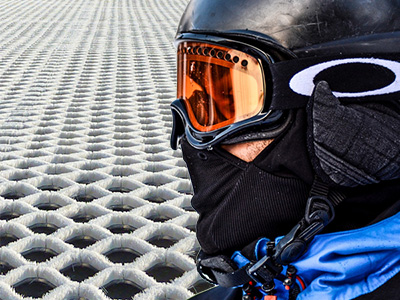 A man wearing skiing goggles and some dry slopes behind him