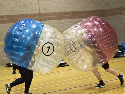Two people running into each other in inflated zorbs