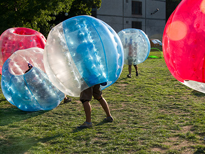 Some people in zorbs playing bubble football