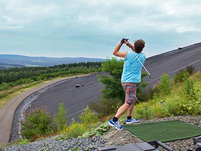 A man firing a golf ball off a high platform