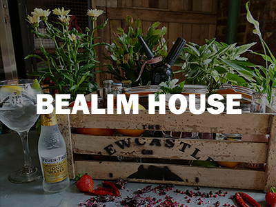 A bottle of gin and a full glass next to it, with the Bealim House logo overlapping