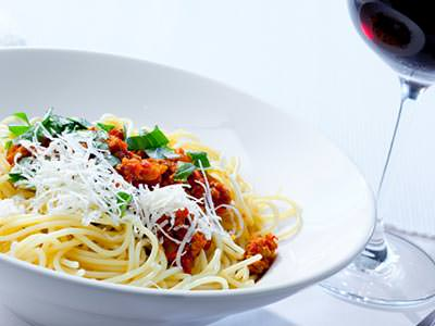 Close up of a white bowl of spaghetti topped with parmesan, next to a glass of red wine