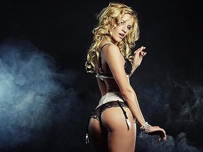 A female stripper in the spotlight wearing just black underwear