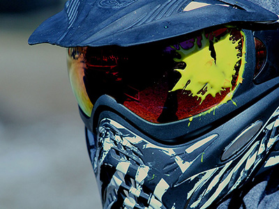 A man wearing a mask, with a paintball splat on his visor