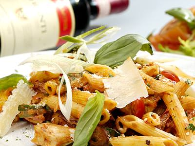 Close up of pasta topped with cheese and rocket, with a red wine bottle on its side in the background
