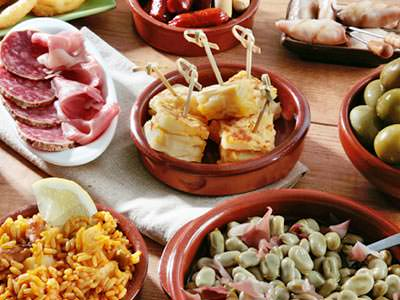 Some tapas food including ham and olives on a table