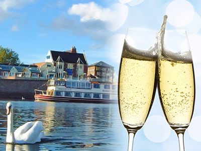 A boat sailing with a swan in the foreground and an image of champagne in glasses overlapping