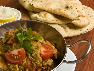 Close up of a silver bowl of curry next to naan breads