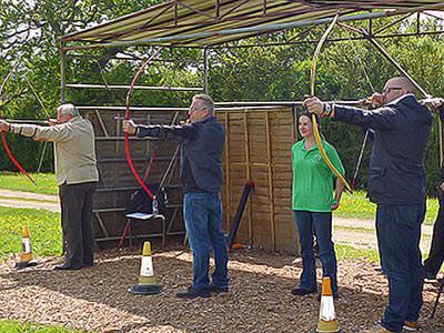 Three men firing arrows under the instruction of a woman in a green shirt