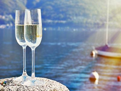 Two full champagne flutes on a rock, with the sea, buoys and a boat in the background