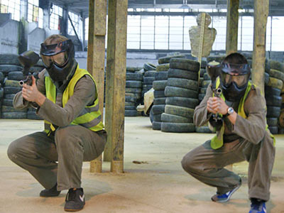 Two people crouching down, holding paintball guns, with tyres stacked up in the background