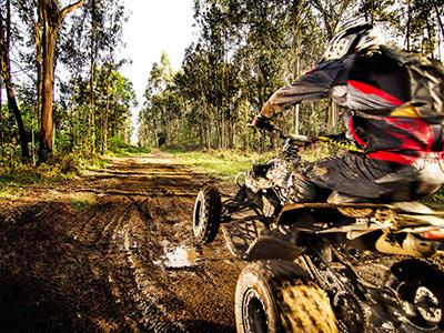 Someone on a quad bike riding through muddy terrain