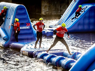A group of people on an inflatable obstacle, on the water