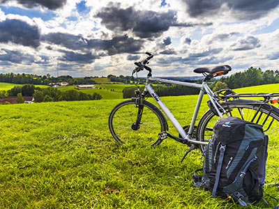 A bike on the grass with a backpack in the foreground