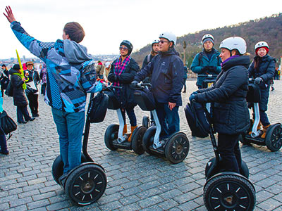 A group of people on segways looking at something someone else is pointing at