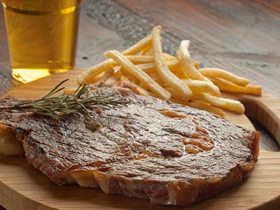 A steak and chips meal with a beer in the background