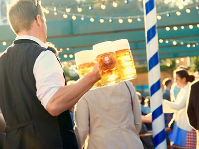 A man holding three steins at an outdoor event