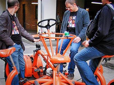 Three men sat on an orange conference bike