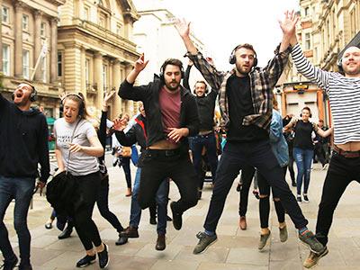 A group of people jumping and wearing headphones in the street