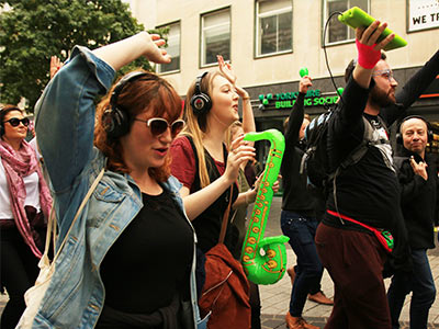A group of people wearing headphones with their hands up in the air