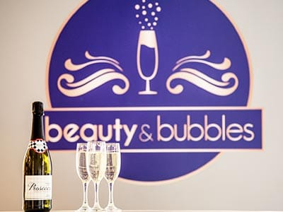 Image of a bottle prosecco with three poured glasses and beauty and bubbles logo on the wall in background