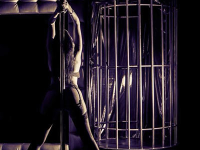 A woman with her back to a pole and a cage in front of her