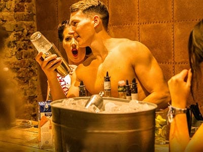 A topless man shaking a cocktail with a bucket of ice in front of him