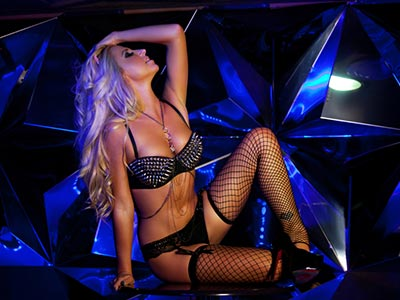 A woman in lingerie and fishnets sitting down, posing