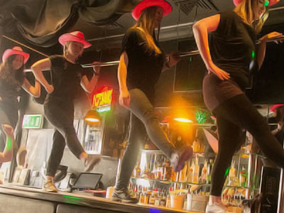 A group of women in pink cowboy hats, dancing on a bar