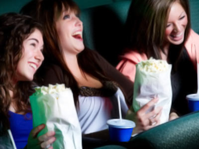 Three girls sitting down with popcorn, laughing