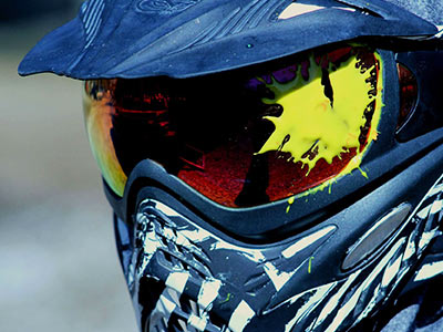 A close up of a person wearing a helmet with a paintball splat on the visor