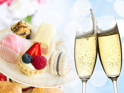 Some cakes on a stand and two glasses of champagne