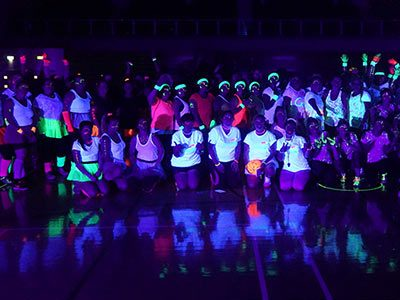 A group of people in the dark wearing glowing headbands and clothes