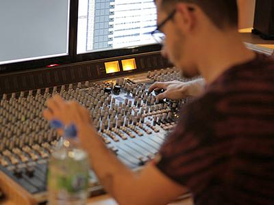 A man working at a large sound mixing desk