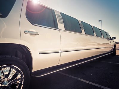 A white limo parked outside, with blue sky in the background