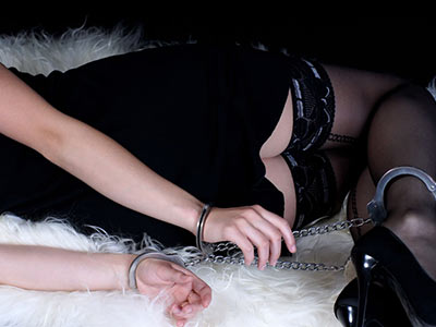 A close up of a woman's hands and feet in handcuffs