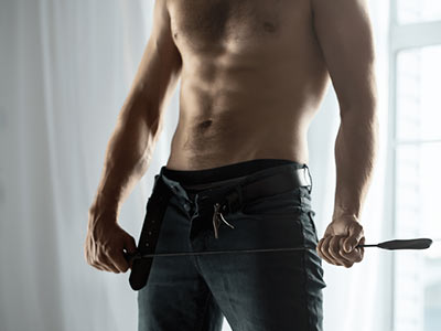 A close up of a topless man, holding a whip