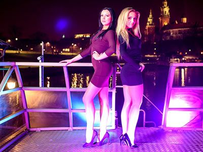 Two girls posing on a boat with a river in the background