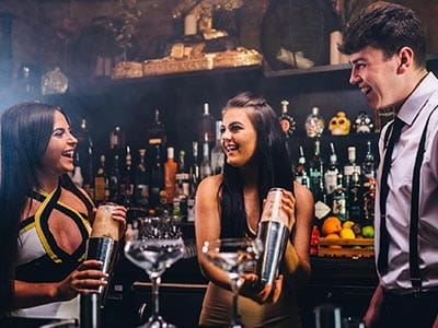 Image of two women standing with a bartender holding cocktail shakers and making cocktails