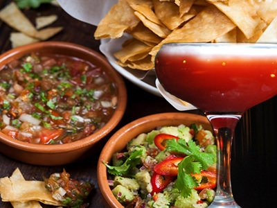 An image of two bowls of food and a bowl of crisps overlaid with a coupe glass filled with red liquid