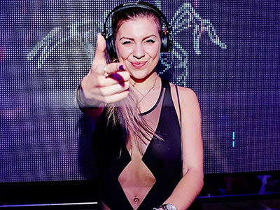 A girl with a pair of DJ headphones on, pointing at the camera