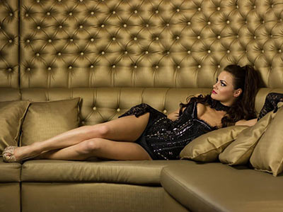 A woman lying down in a corset on a gold sofa