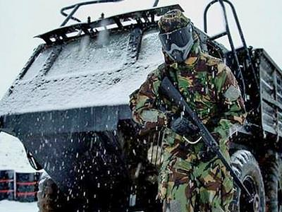 A man wearing camouflage overalls and a mask standing in front of a large, snow-covered military vehicle