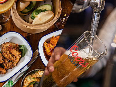 Image of two pints of lager and two small pans filled with food on a wooden tray