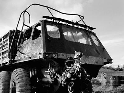 A black and white image of a large vehicle with a man crouched in front aiming a paintball gun
