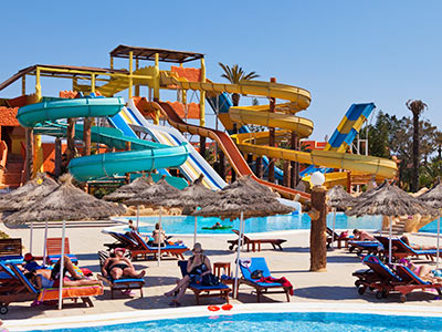 A water park with slides in the background and a pool in the foreground