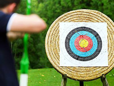 A man aiming a bow and arrow at a wicker archery target
