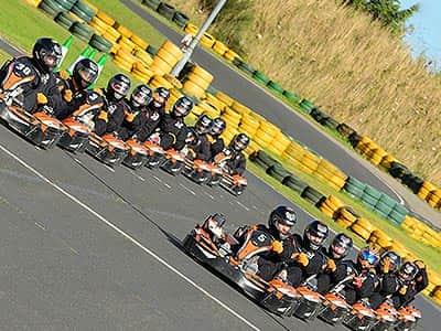 Multiple go karts racing on an outdoor track