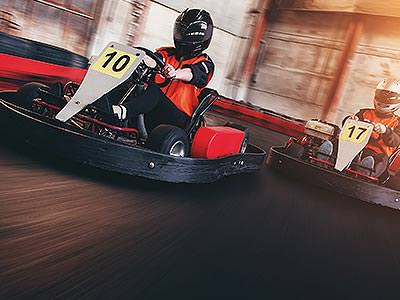 Two go karts racing on an indoor circuit
